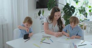 Due bambini dei ragazzi disegnano con sua madre che si siede nella cucina Famiglia felice nel paese I fratelli disegnano alla tav video d archivio