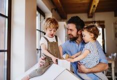 Due bambini del bambino con il padre che gioca con la casa della carta all'interno a casa fotografia stock