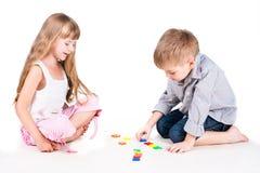 Due bambini di gioco con l'alfabeto isolato su bianco Immagine Stock Libera da Diritti
