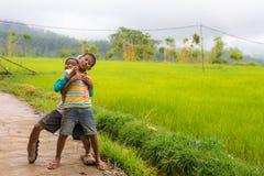 Due bambini divertenti non identificati che giocano, sorridenti ed esaminanti la macchina fotografica nel coun scenico Fotografia Stock