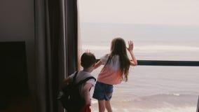 Due bambini emozionanti felici che corrono fino alla finestra grande dell'appartamento dell'hotel per godere del movimento lento  stock footage