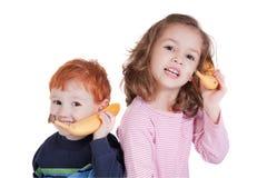 Due bambini felici che comunicano sui telefoni della banana Fotografie Stock