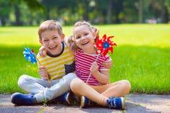 Due bambini felici che giocano con il mulino a vento fotografia stock