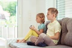Due bambini felici che giocano i video giochi a casa Fotografie Stock Libere da Diritti