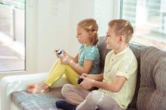 Due bambini felici che giocano i video giochi a casa Immagini Stock Libere da Diritti