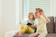 Due bambini felici che giocano i video giochi a casa Fotografia Stock Libera da Diritti