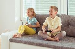 Due bambini felici che giocano i video giochi a casa Immagini Stock