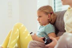 Due bambini felici che giocano i video giochi a casa Immagine Stock Libera da Diritti