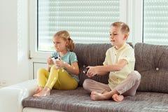 Due bambini felici che giocano i video giochi a casa Fotografia Stock