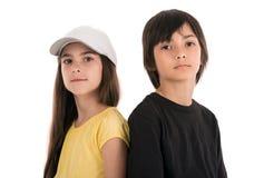 Due bambini felici che posano con le racchette di tennis sul backgrou bianco Immagini Stock