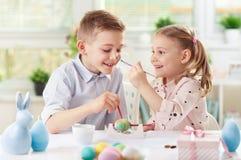 Due bambini felici che si divertono durante la pittura eggs per pasqua dentro immagine stock libera da diritti