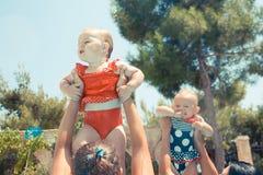 Due bambini felici con le madri che giocano nello stagno Fotografie Stock