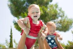 Due bambini felici con le madri che giocano nello stagno Fotografia Stock Libera da Diritti