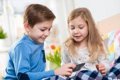Due bambini felici dei fratelli germani musica divertentesi e d'ascolto con fotografia stock