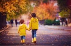 Due bambini felici, fratelli che camminano insieme sulla via di autunno in impermeabili gialli e stivali di gomma fotografia stock