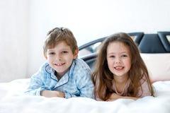 Due bambini felici in pigiami che celebrano pigiama party Scuola materna e ragazzo e ragazza di scuola divertendosi insieme Fotografie Stock Libere da Diritti