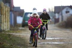 Due bambini felici ragazzo e la guida della ragazza va in bicicletta all'aperto nel freddo fotografia stock libera da diritti