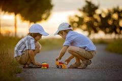 Due bambini, fratelli del ragazzo, divertendosi all'aperto con le automobili del giocattolo Fotografia Stock