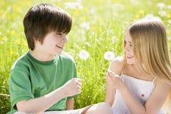 Due bambini in giovane età che si siedono all'aperto Fotografie Stock