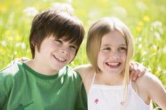 Due bambini in giovane età che si siedono all'aperto braccio in braccio Fotografie Stock Libere da Diritti