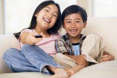 Due bambini in giovane età nella sala con telecomando Fotografia Stock