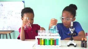 Due bambini misti afroamericani che verificano esperimento del laboratorio di chimica stock footage