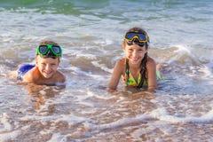 Due bambini nelle maschere di immersione subacquea sul mare Fotografia Stock