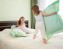 Due bambini o bambini che giocano o hanno battaglia con i cuscini in camera da letto Fotografie Stock Libere da Diritti