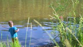 Due bambini pescano il pesce con le canne da pesca sulla sponda del fiume Bello paesaggio di estate Ricreazione esterna archivi video