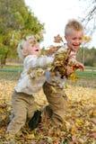 Due bambini piccoli che gettano la caduta va fuori fotografie stock