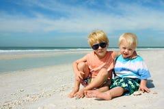Due bambini piccoli che si siedono sulla bella spiaggia Immagini Stock