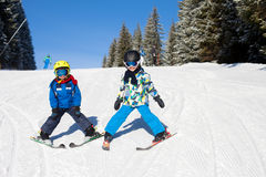 Due bambini piccoli, fratelli dei fratelli germani, scianti nel mounta austriaco Fotografia Stock