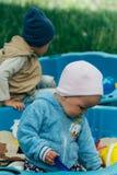 Due bambini si siedono nella sabbiera e giocano con le pale, i rastrelli, giocattoli fotografia stock