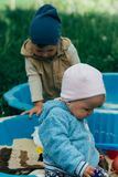 Due bambini si siedono nella sabbiera e giocano con le pale, i rastrelli, giocattoli fotografie stock libere da diritti