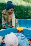 Due bambini si siedono nella sabbiera e giocano con le pale, i rastrelli, giocattoli immagine stock libera da diritti