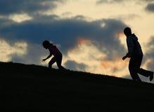 Due bambini slhouetted contro un cielo di tramonto Fotografie Stock Libere da Diritti