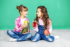 Due bambini sono parlanti e beventi il succo Ragazze con pineappl immagini stock libere da diritti