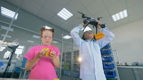 Due bambini stanno giocando con un quadcopter, fuco in un laboratorio video d archivio