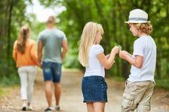 Due bambini stranamente raccolgono le foglie immagine stock libera da diritti