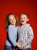 Due bambini su colore rosso Fotografia Stock Libera da Diritti