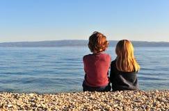 Due bambini sulla spiaggia sul tramonto immagine stock libera da diritti