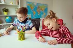 Due bambini svegli che disegnano con le matite variopinte immagine stock libera da diritti