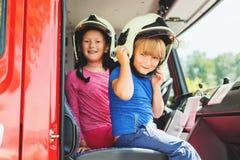 Due bambini svegli che giocano in camion dei vigili del fuoco Fotografia Stock Libera da Diritti