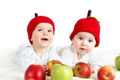 Due bambini svegli che si trovano in cappelli sulla coperta molle con le mele Fotografia Stock Libera da Diritti