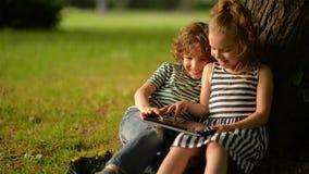 Due bambini svegli facendo uso della compressa digitale di estate fanno il giardinaggio archivi video