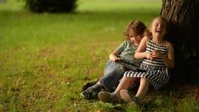 Due bambini svegli facendo uso della compressa digitale di estate fanno il giardinaggio video d archivio