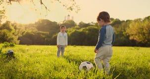 Due bambini svegli, giocare a calcio insieme, estate Giocar a calcioe dei bambini all'aperto video d archivio