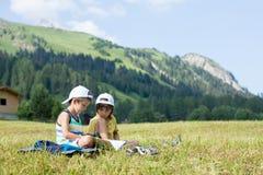 Due bambini svegli, leggenti un libro su un prato inglese in alpi svizzere Immagini Stock Libere da Diritti