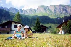 Due bambini svegli, leggenti un libro su un prato inglese in alpi svizzere Fotografia Stock