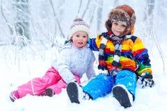 Due bambini svegli ragazzo e ragazza nella foresta nevosa di inverno al fondo dei fiocchi di neve svago e stile di vita di aria a fotografia stock